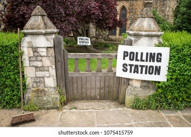 British election polling station sign hanging on post next to a gate and hedge in the UK