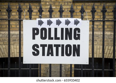 British election polling station sign hanging on classic wrought iron fence in front of yellow brick wall in London, UK