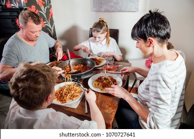British family enjoying a spagetti bolognese together at home. They are sitting at the dining table with the baby girl in a baby seat.