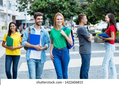 British female student and brazilian guy with group of mutliethnic students outdoor in city in summer