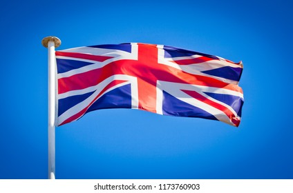 British flag blowing in strong wind against pure blue sky. Union Jack, symbol of national patriotism.
