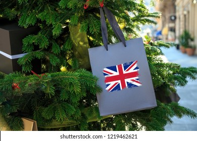 British flag printed on a Christmas shopping bag. Close up of a shopping bag as a decoration on a Xmas tree on a street in Great Britain. Christmas shopping, local market sale and deals concept.