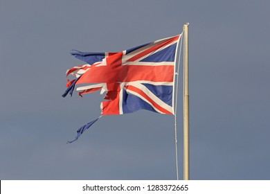 British flag or Union Jack torn and tattered flying in the winter by the sea in Italy representing the disaster