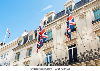 British flags flying on the balcony of a historic building in central London