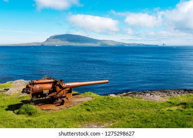 British gun from the warship  in Skansin fortress of Torshavn,  Faroese island of Streymoy. Atlantic Ocean and Nolsoy island are at background