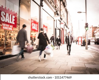 British high street scene with prominent SALE sign in shop window and anonymous shoppers walking by carrying shopping bags