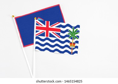 British Indian Ocean Territory and Guam stick flags on white background. High quality fabric, miniature national flag. Peaceful global concept.White floor for copy space.