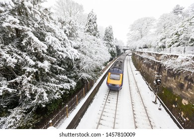 A British  intercity train travelling at speed through a snow-covered park in Bath, United Kingdom