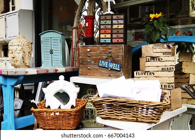 "British junk shop with baskets, a bust and other bric-a-brac, with the positive message ""Live Well"""
