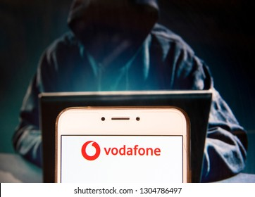 British multinational telecommunications corporation and phone operator Vodafone logo is seen on an Android mobile device with a figure of hacker in the background.