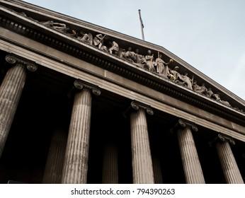 British Museum facade segment against blue sky. Located in Bloomsbury, London.