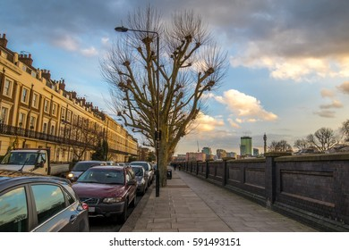 British neighborhood facing the city center with very tall buildings in the background during sunset. Many cars parked in the road dificulting the passage of others