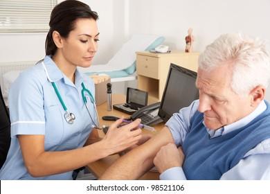 British nurse giving injection to senior man