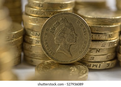British pound coins neat stacks up close macro studio shot against a shiny reflective White background