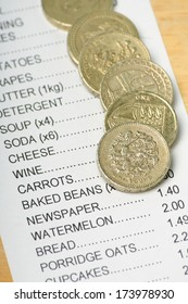 British Pound Coins on a Receipt for Food Shopping as a concept for rising prices and the cost of living.