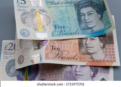 British Pound Sterling notes. Showing the new five,ten and twenty pound notes on top of each other on a grey background. All these notes are now printed on mostly plastic replacing the old paper ones.