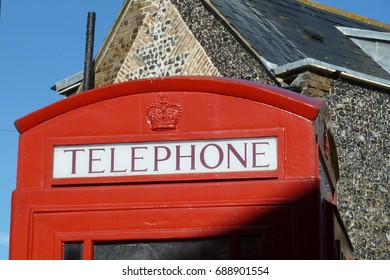 British red telephone box in front of a building and blue sky background