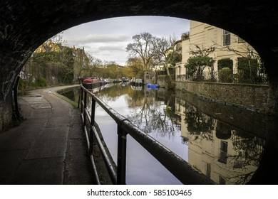 A british river canal with a bridge and house boats in the banks