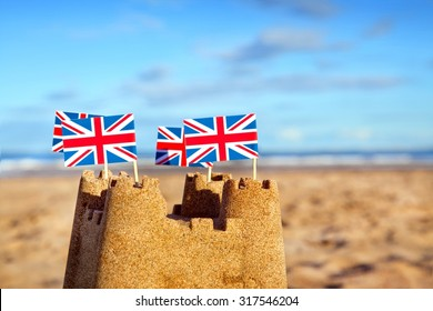 British seaside traditional sand castle on the beach with Union Jack Flags