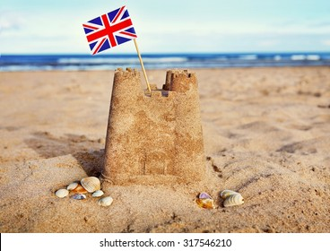British Seaside traditional sand castle on the beach with Union Jack flag and shells