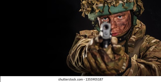 British soldier aiming with black pistol. Image on a dark background.