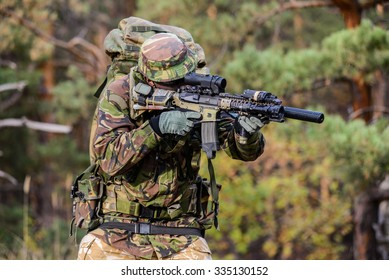 British soldier with military backpack aiming from his rifle in forest/Gunner aims in forest