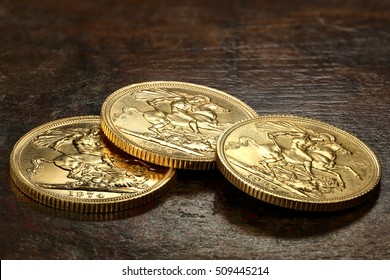 British Sovereign gold coins on rustic wooden background