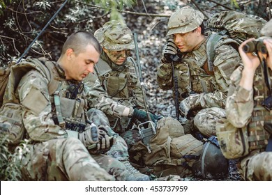 British special forces soldiers with weapon and officer holds a radio station, and give orders subdivision. war, army, technology and people concept. officer