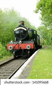 british steam train arriving at a rural platform