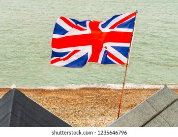 British Union Jack flag flying from a pole on beach huts at the edge of the sea on a pebble beach in Kent, England