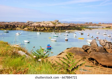 Brittany, France. Boats and people at Pink Granite Coast during low tide. The coast between Perros-Guirec and Ploumanach is one of the most popular Breton resorts for family vacation.
