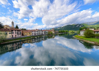 Brivio, Lombardia, Italy: Riverfront. Blue sky with heap clouds reflecting in the flooded river in April.