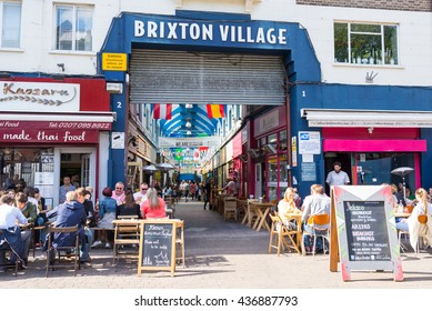 Brixton, London, UK - 15 May 2016: People eating outside the main entrance of Brixton Village Market, a multicultural community market with independent shops and ethnic restaurants in South London.