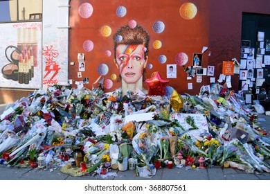 BRIXTON, LONDON, UNITED KINGDOM- January 28, 2016: Flowers left beneath a mural as fans paying tribute to David Bowie in his birthplace. Bowie was born as David Robert Jones in Brixton, London, UK.