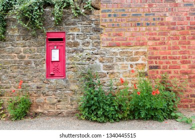 Brixworth, Northamptonshire / UK - May 29th 2018: A red village post box set into a stone wall. Ivy hangs over the top of the wall and at the bottom poppies and nettles are growing.