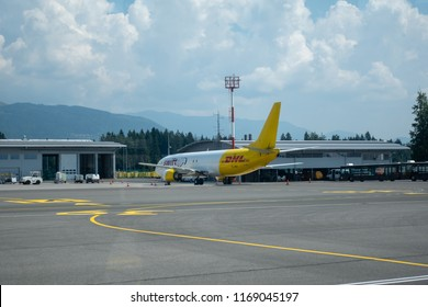 Brnik, Slovenija - August 23 2018: Swift Air Boeing B737 with yellow DHL logo on tail at Ljubljana Airport waiting for cargo on tarmac.