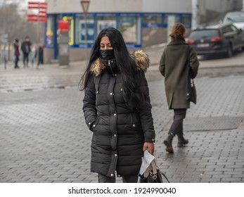 Brno, Czech Republic. 02-17-2021. Young woman dress in black with face mask to protect from corona virus walk on Halvni Nadrazi main tram station in the city center of Brno during winter.
