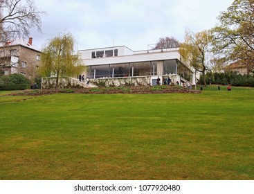 BRNO, CZECH REPUBLIC - APRIL 13, 2018: Garden view of the Villa Tugendhat with visitors on the terrace. The Villa of Greta and Fritz Tugendhat was designed by Ludwig Mies van der Rohe.