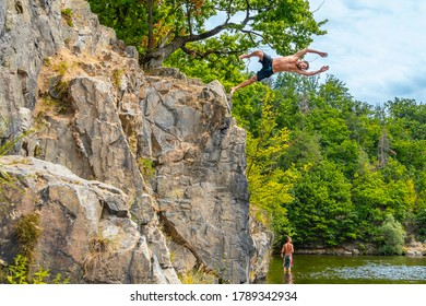 BRNO, Czech Republic -  August, 2 2020: Man jumping from a cliff into the water. Dangerous jump into the water. Water jump from the rock. Shallow water injury.