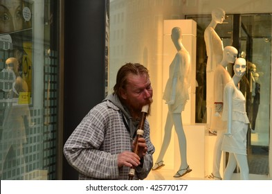 BRNO, THE CZECH REPUBLIC - MAY 12, 2016: Street musician plays the flute. Boutique display window with mannequins in fashionable dresses.