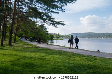 Brno, Czech Republic - May 15 2019: people walking along the shore of the lake Brno Dam reservoir lake