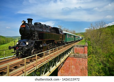 Brno, Czech republic, May 19th, 2019. Beautiful old steam train driving along a bridge in the countryside. Concept for travel, transportation and retro old style.