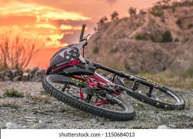 Brno Hady/Czech Republic-03.30.2018: Red mountain bike on the ground with black full face helmet.