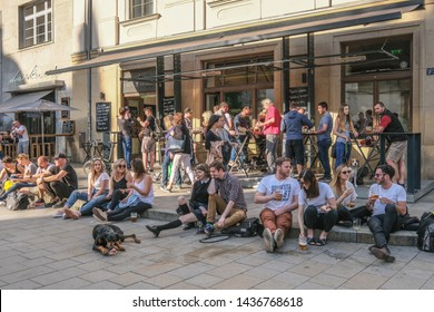 Brno, Moravia, Czech Republic - May 31, 2019: Young women and men having good time, drinking beer and chatting around and on the sidewalks of St. James square at weekend early eve Friday