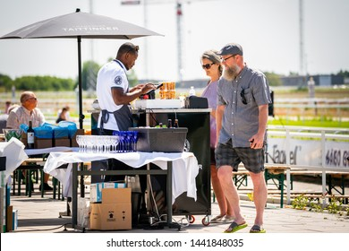 BRO, SWEDEN - JUNE 30, 2019: Customers and staff at an outdoor restaurant with a drink stand, incidental people in the background in Bro Sweden June 30, 2019.