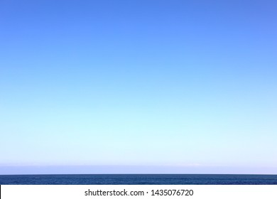 Broad background of the sky with gradient blue color and calm ocean at the bottom of the photo.