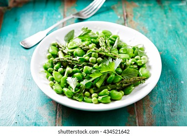 Broad Bean, Green Pea and Asparagus Salad with Herbs. Homemade food. Concept for a tasty and healthy vegetarian meal. Copy space.