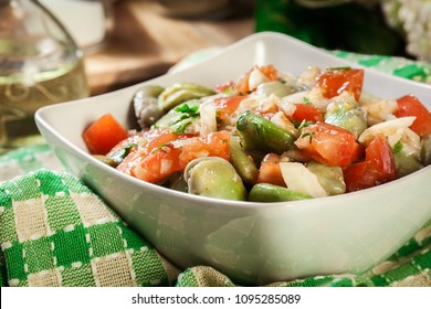 Broad bean salad with tomatoes, onion and olive in white bowl