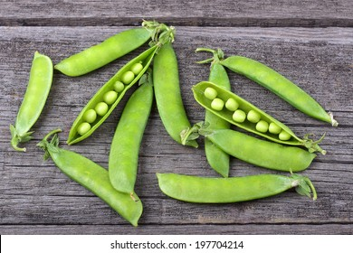 Broad beans of peas on old wood background