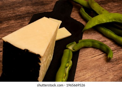 Broad beans and pecorino cheese on black cutting board, over a wooden table